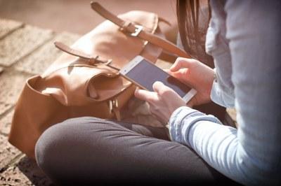 Eine Frau tippt auf ihrem Smartphone