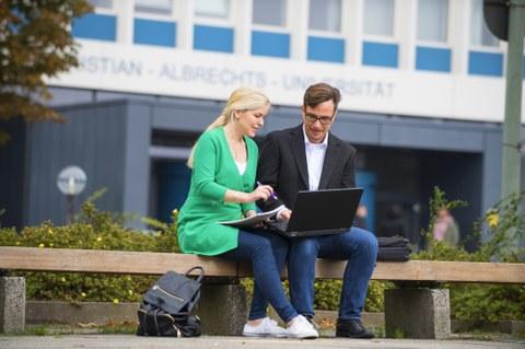 Studierende und Alumnus mit Laptop