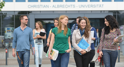 Students in front of the university main building. In the background the letters on the building: Christian-Albrechts-Universität
