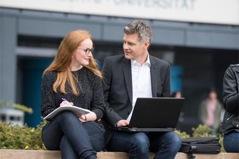 Studierende und Alumnus schauen sich etwas auf dem Laptop an